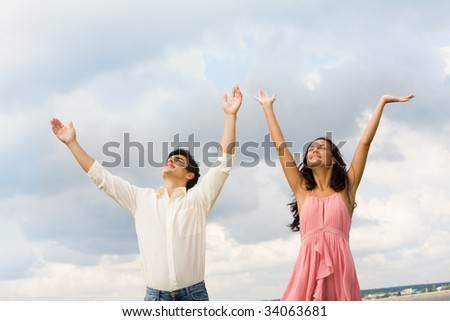 Portrait of happy couple standing with raised arms on background of cloudy sky - stock photo