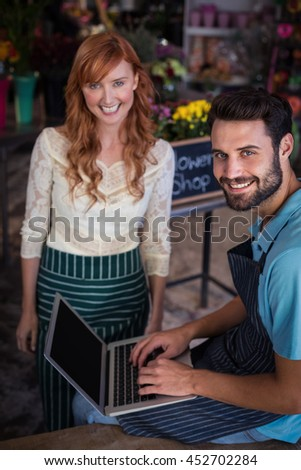 Portrait of happy couple using laptop in the flower shop