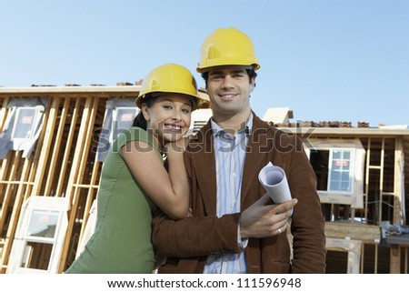 Portrait of happy couple wearing hardhat at construction site