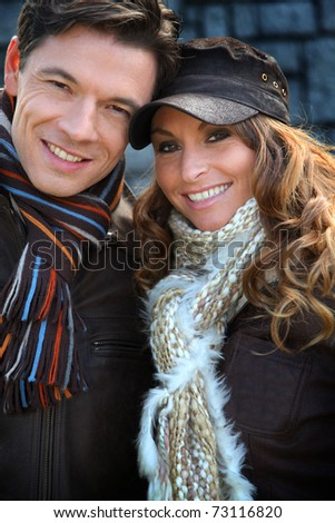 Portrait of happy couple wearing scarves in winter time - stock photo