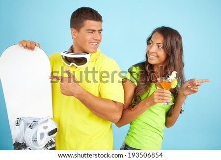 Portrait of happy couple with cocktail and skateboard looking at one another and pointing at opposite sides - stock photo
