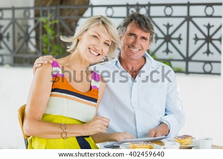 Portrait of happy couple with digital tablet sitting at cafe