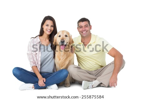 Portrait of happy couple with dog sitting over white background - stock photo