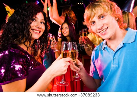 Portrait of happy couple with flutes of champagne toasting at birthday party