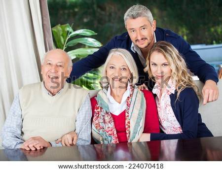 Portrait of happy couple with grandparents at nursing home - stock photo