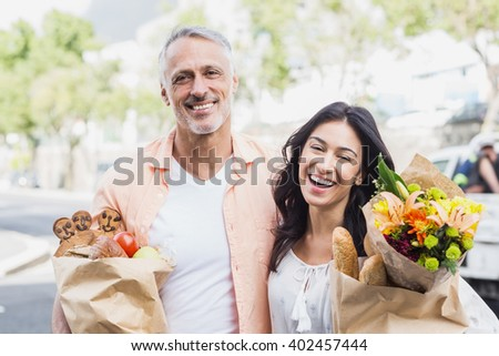 Portrait of happy couple with grocery bags standing outdoors - stock photo