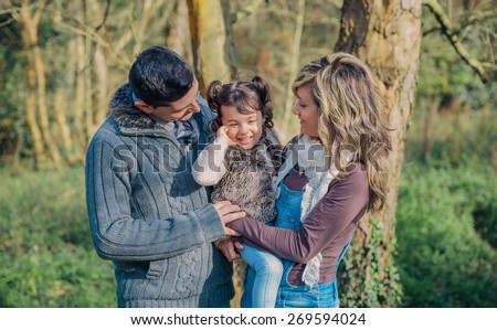 Portrait of happy couple with her little daughter enjoying together leisure over a forest background. Family time concept. - stock photo