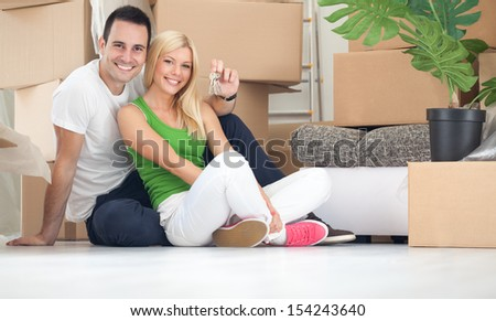 Portrait of happy couple with key of new home - stock photo