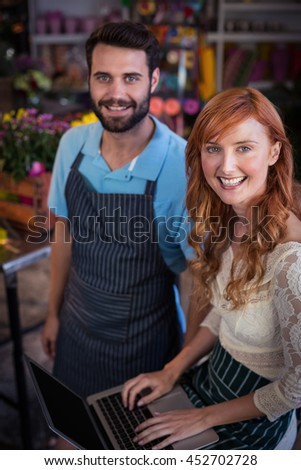 Portrait of happy couple with laptop in the flower shop - stock photo