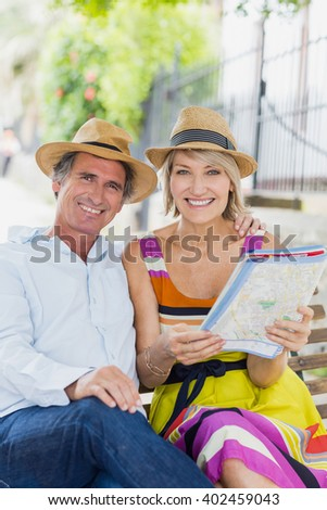 Portrait of happy couple with map sitting on bench in park