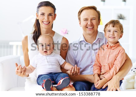 Portrait of happy couple with their two sons looking at camera