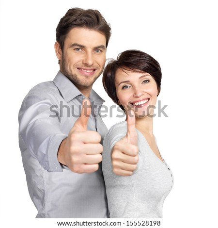 Portrait of happy couple with thumbs up sign isolated on white background - stock photo