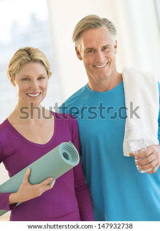 Portrait of happy couple with water bottle, exercise mat and towel in gym