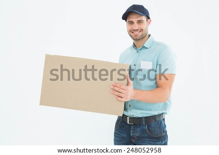 Portrait of happy courier man carrying cardboard box on white background - stock photo