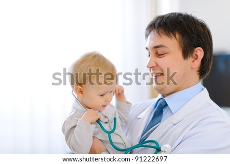 Portrait of happy cute baby with stethoscope on hands of pediatrician - stock photo