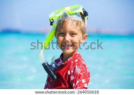Portrait of happy cute boy wearing snorkeling mask ready to dive in the sea - stock photo