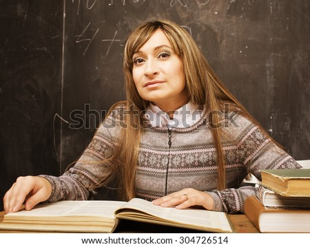 portrait of happy cute brunette emothional student in classroom at blackboard close up