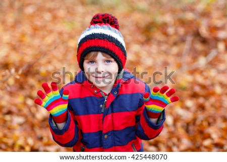 Portrait of happy cute little kid boy with autumn leaves background in colorful clothing. Funny child having fun in fall forest or park on cold day. With hat and gloves - stock photo