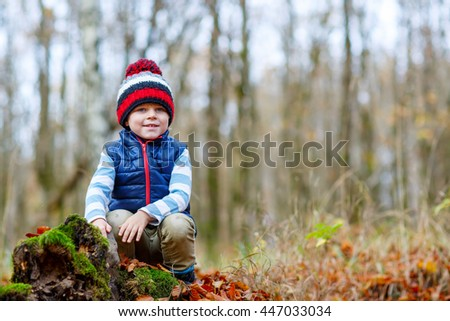 Portrait of happy cute little kid boy with autumn leaves background in colorful clothing. Funny child having fun in fall forest or park on cold day.