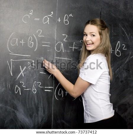 portrait of  happy cute student near blackboard - stock photo