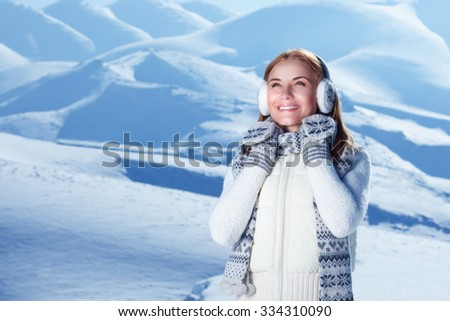 Portrait of happy cute woman standing outdoors and wearing beautiful warm knitted set, spending winter holidays in the snowy mountains - stock photo
