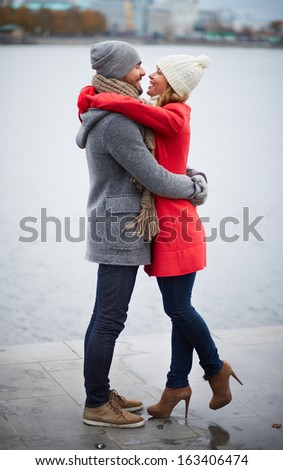 Portrait of happy dates in coats embracing outdoors - stock photo