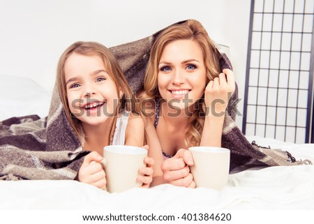 Portrait of happy daughter and mother lying under plaid with cups of tea - stock photo