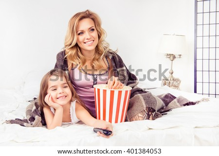 Portrait of happy daughter and mother watching cartoons with popcorn