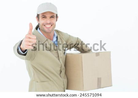 Portrait of happy delivery man gesturing thumbs up while carrying box over white background - stock photo