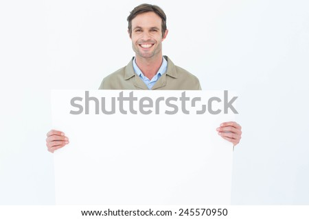 Portrait of happy delivery man holding blank billboard against white background - stock photo