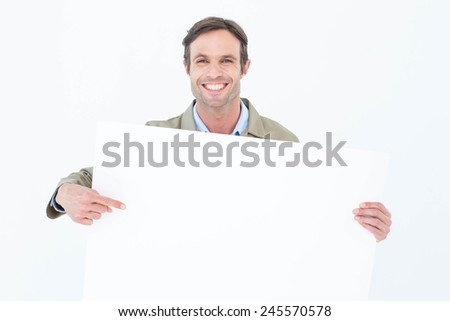 Portrait of happy delivery man pointing at blank billboard against white background - stock photo