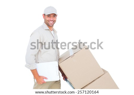 Portrait of happy delivery man pushing trolley of boxes on white background - stock photo