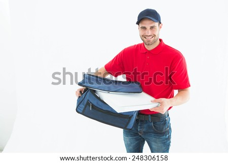 Portrait of happy delivery man removing pizza box from bag on white background - stock photo