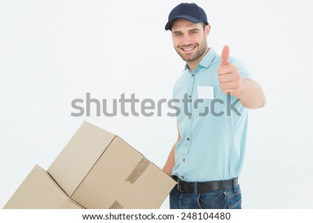Portrait of happy delivery man with cardboard boxes gesturing thumbs up on white background - stock photo