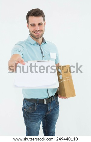 Portrait of happy delivery man with package giving clipboard for signature on white background - stock photo