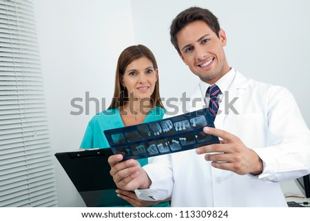 Portrait of happy dentist with dental nurse analyzing X-ray report in clinic - stock photo