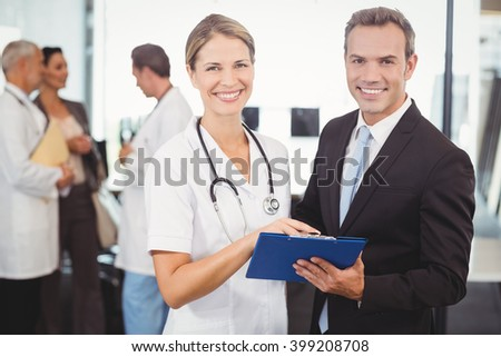Portrait of happy doctors with clipboard in hospital - stock photo