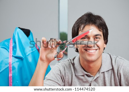 Portrait of happy dressmaker holding scissor with mannequin in background - stock photo