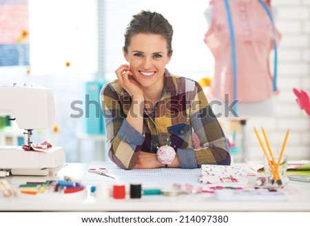 Portrait of happy dressmaker woman in studio - stock photo