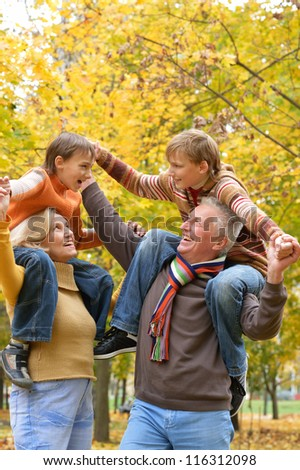 portrait of happy elderly couple and children rest fall