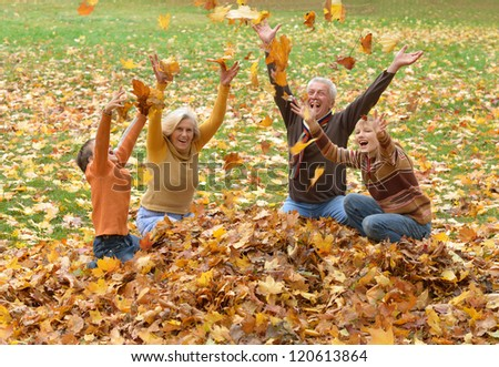 portrait of happy elderly couple and children throwing leaves - stock photo