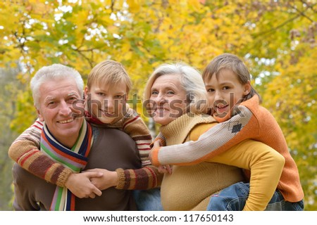 portrait of happy elderly couple and grandchildren resting in autumn