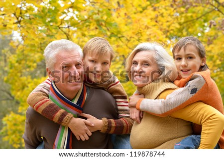 portrait of happy elderly couple and grandchildren resting in autumn - stock photo