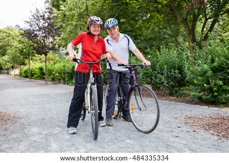 Portrait Of Happy Elderly Couple With Their Bicycles