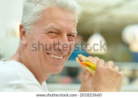 Portrait of happy elderly man eating fast food