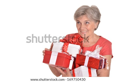Portrait of happy elderly woman holding gifts on white background