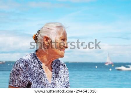 Portrait of happy elderly woman on the seaside - stock photo
