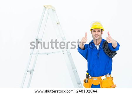 Portrait of happy electrician gesturing thumbs up while standing by ladder over white background - stock photo