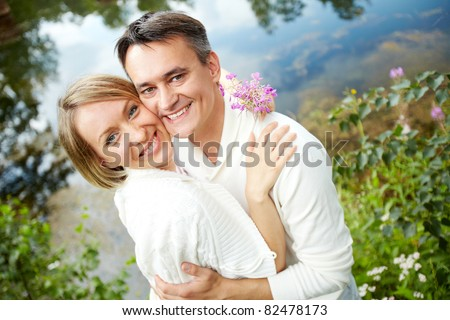 Portrait of happy embracing couple looking at camera