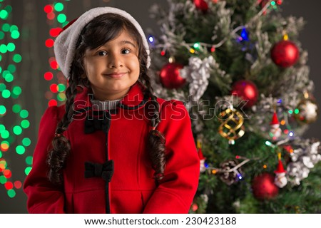 Portrait of happy excited girl on the background of Christmas tree - stock photo